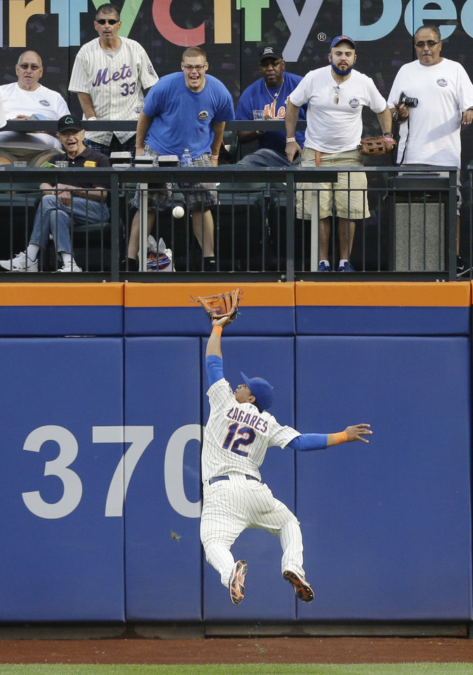 Photo - New York Mets center fielder Juan Lagares (12) jumps to catch a ball hit by San Francisco Giants' Brandon Belt for an out in the second inning of a baseball game Saturday, Aug. 2, 2014, in New York. (AP Photo/Frank Franklin II)