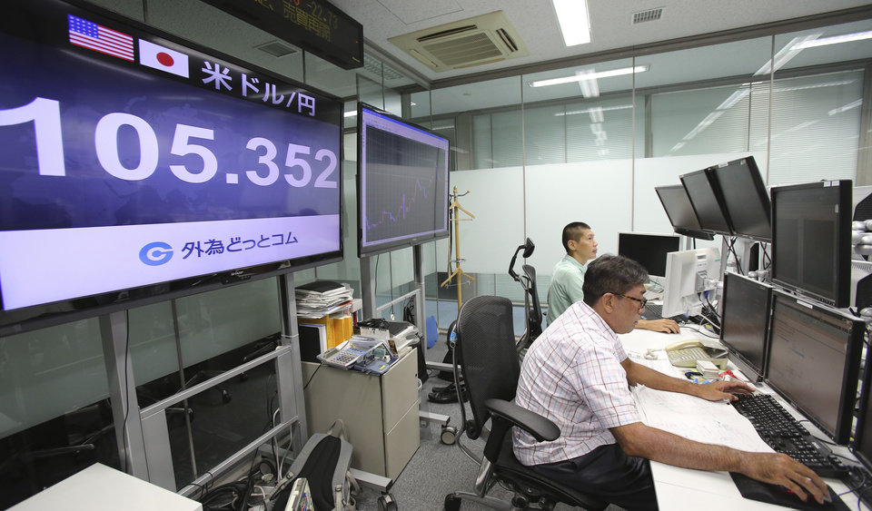 Photo - Money traders of a foreign exchange company work at an electric monitor displaying the current exchange rate of Japanese yen against U.S. dollar in Tokyo, Friday, Sept. 5, 2014. The U.S. dollar rose to around 105.70 yen, the highest since October 2008, on Friday morning. (AP Photo/Koji Sasahara)