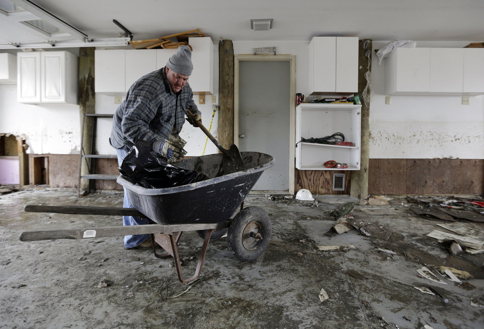 Photo -   Matthew Cafone cleans out debris from his father's house on Cedar Bonnet Island, N.J., Saturday, Nov. 3, 2012, after it was damaged by surge from Superstorm Sandy. (AP Photo/Patrick Semansky)