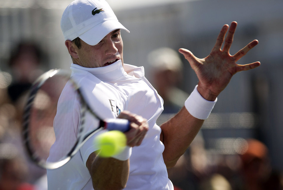 Photo - John Isner, of the United States, returns the ball to Ivan Dodig, of Croatia, during the Sony Open tennis tournament, Saturday, March 23, 2013, in Key Biscayne, Fla. (AP Photo/J Pat Carter)