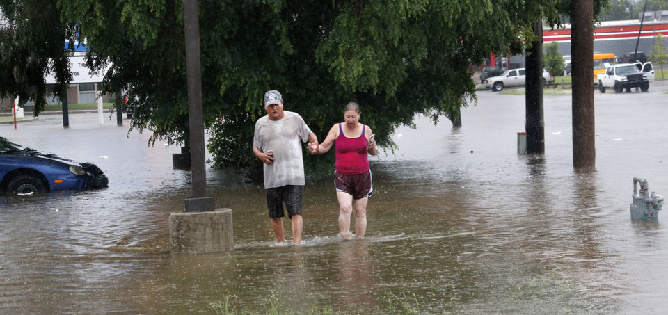 Photo - A couple walks through deep water on a sidewalk along S. May Avenue on Thursday, June 6, 2019, after heavy rains overwhelmed stormwater drainage systems, flooding streets, requiring  high water rescues in Oklahoma City as another round of severe storms passes through the metro. The National Weather Service reports up to 1.5 inches of rain fell during a 30-minute period Thursday, June 6, 2019,  in the western part of the Oklahoma City area.  Firefighters said they assisted four people to safety between 11 o'clock and noon in the deep water that flooded this intersection at SW 29 and May.  [Jim Beckel/The Oklahoman]