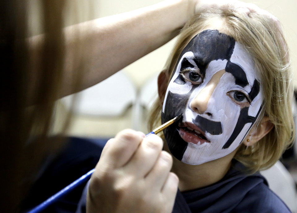 Photo - Pond Creek-Hunter fan Emilie Davis has her face painted for the Class A girls high school basketball state championship game between Seiling and Pond Creek-Hunter at the State Fair Arena in Oklahoma City, Okla., on Saturday, March 8, 2014.  Photo by Chris Landsberger, The Oklahoman