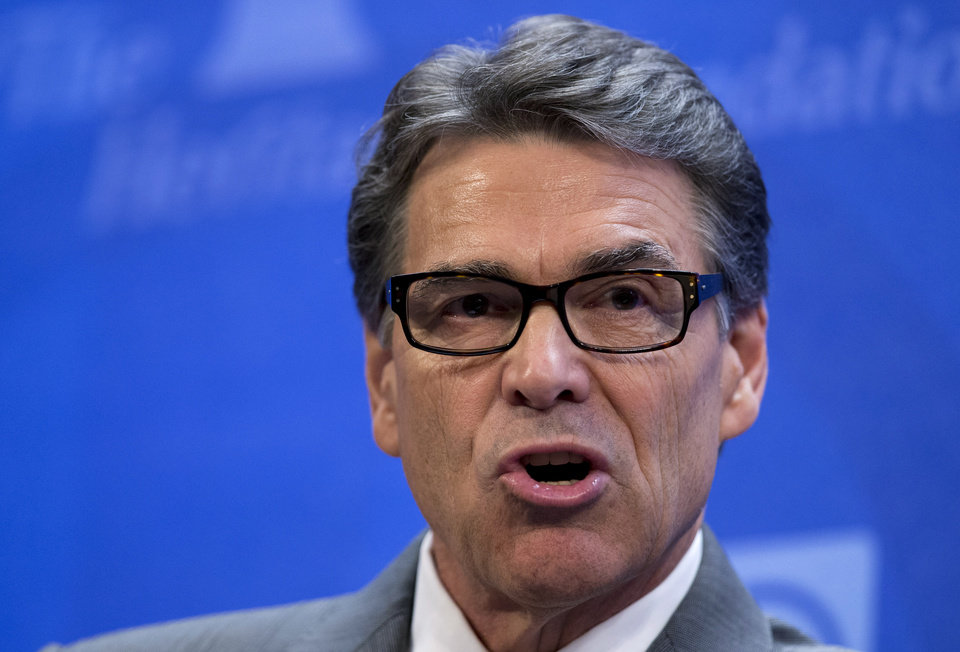 Photo - Texas Gov. Rick Perry speaks at the Heritage Foundation in Washington, Thursday, Aug. 21, 2014, about that he would be open to sending U.S. combat forces to Iraq to fight the deadly Islamic state after its attacks on a Christian minority and the beheading of an American journalist and border security. (AP Photo/Manuel Balce Ceneta)