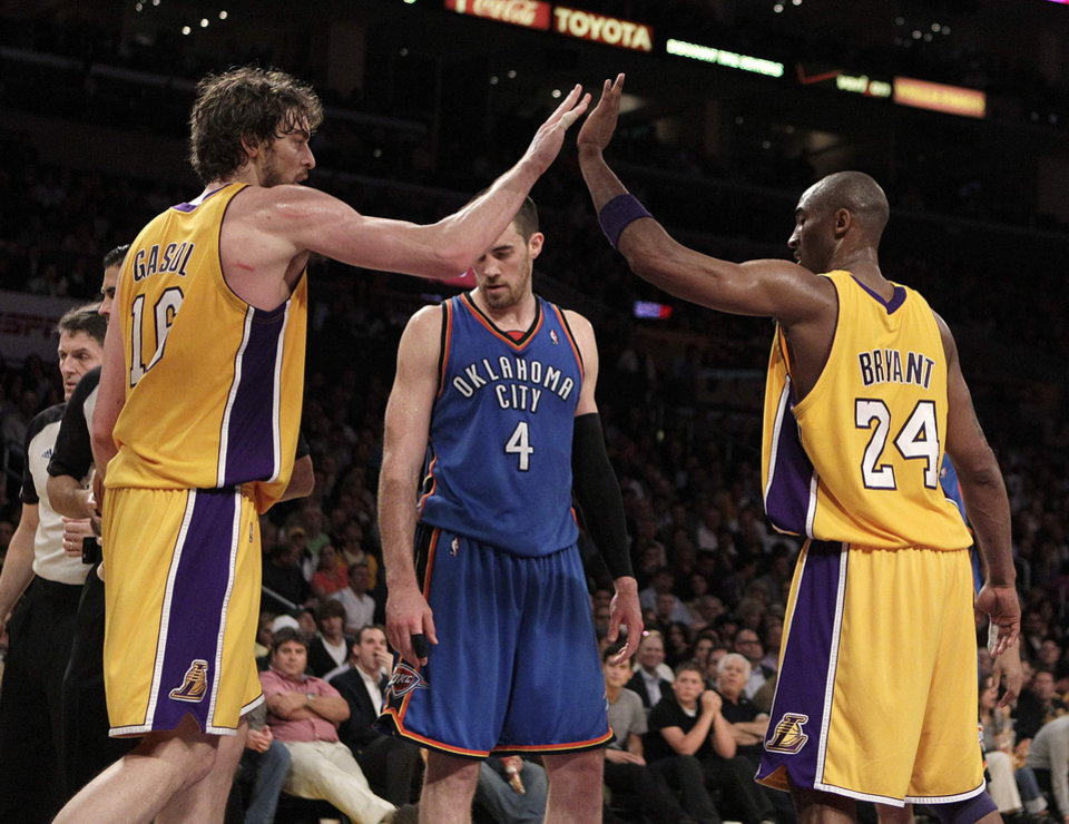 Photo - Los Angeles Lakers guard Kobe Bryant, right, and Pau Gasol, of Spain, high-five during the second half of Game 2 in a first-round NBA basketball playoff series in Los Angeles, Tuesday, April 20, 2010.  Standing in the middle is Oklahoma City Thunder forward Nick Collison. The Lakers won 95-92. (AP Photo/Jae C. Hong) ORG XMIT: LAS212