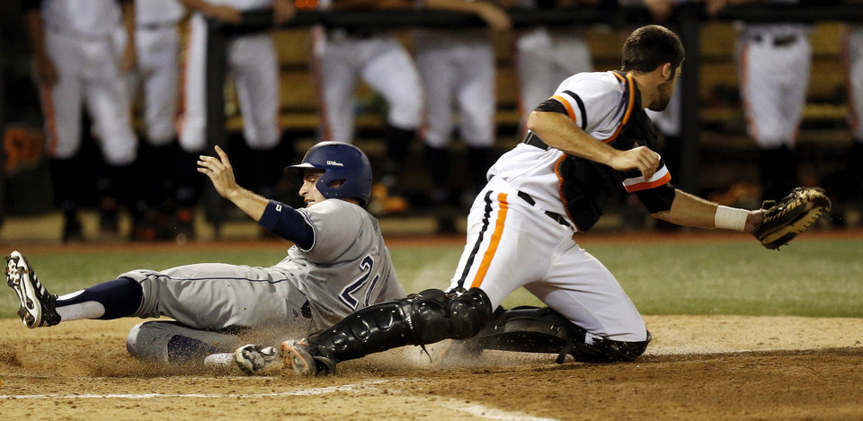 Photo - UC Irvine's Kris Paulino (24) slides home to score past OSU's Bryan Case (34) in the 4th inning during Game 1 of the NCAA baseball Stillwater Super Regional between Oklahoma State and UC Irvine at Allie P. Reynolds Stadium in Stillwater, Okla., Friday, June 6, 2014. Photo by Nate Billings, The Oklahoman