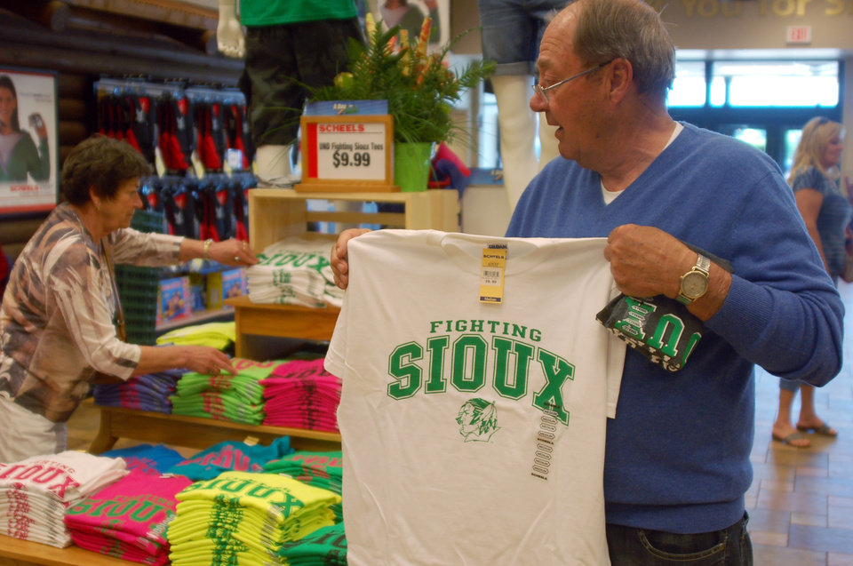 Photo - FILE - In this, Tuesday, June 12, 2012, file photo, Buck Striebel holds up a University of North Dakota Fighting Sioux T-shirt while his wife, GaeLynn, sorts through other shirts on sale at a sporting goods store in Bismarck, N.D. The decades-old debate over whether to keep the University of North Dakota's Fighting Sioux nickname finally seemed to come to an end as 68 percent of voters in the June primary agreed it was time to drop the nickname deemed