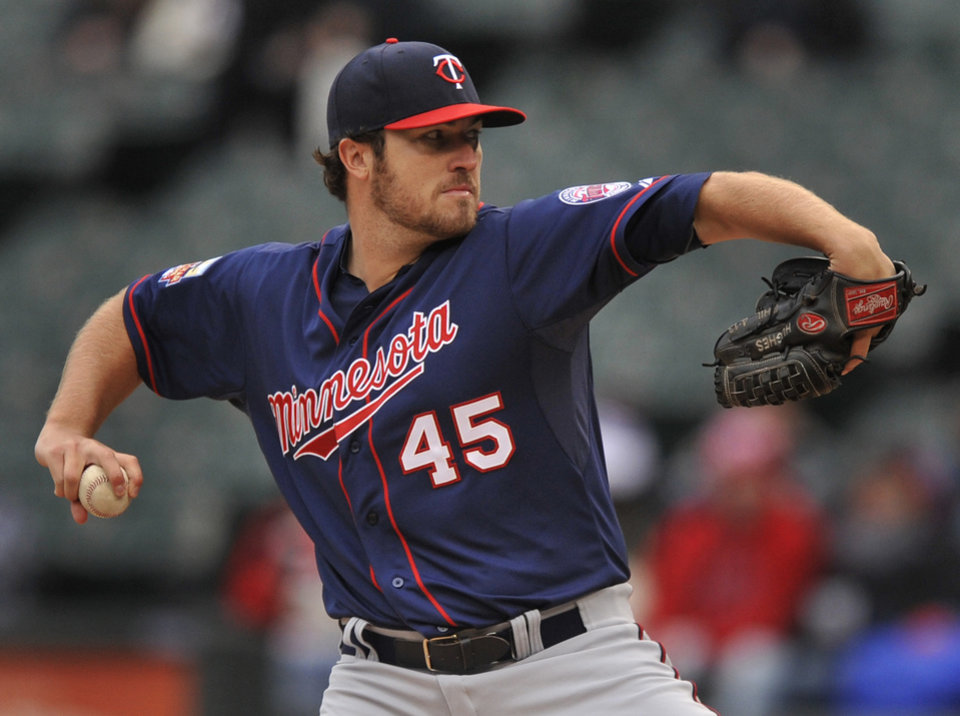 Photo - Minnesota Twins starter Phil Hughes delivers a pitch during the first inning of a baseball game against the Chicago White Sox in Chicago, Thursday, April 3, 2014. (AP Photo/Paul Beaty)