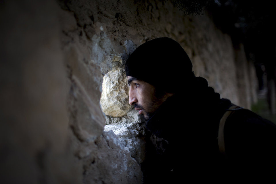 A Free Syrian Army fighter scans for Syrian Army positions during an attack on a military academy in Tal Sheer village, north of Aleppo province, Syria, Thursday, Dec. 13, 2012. (AP Photo/Manu Brabo) ORG XMIT: CAI120