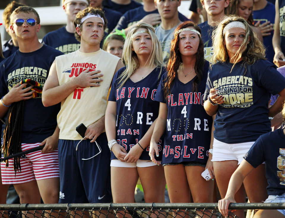 Photo - Southmoore students pause during a moment of silence for tornado victims before a high school football game between Southmoore and Carl Albert at Moore Schools Stadium in Moore, Okla., Thursday, Sept. 5, 2013.  Photo by Nate Billings, The Oklahoman