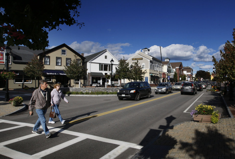 Photo -   A couple crosses Route 1 in downtown Kennebunk, Maine, Friday, Oct. 12, 2012. Curious residents in this seaside community may have to wait to learn which of their friends and neighbors stand accused of giving business to a fitness instructor charged with running a prostitution operation out of her Zumba studio. The police department's plan to release some of the more than 150 names of suspected clients was delayed Friday by last-minute legal wrangling. Alexis Wright, a 29-year-old fitness instructor from Wells, Maine, has pleaded not guilty to prostitution, invasion of privacy and other charges for allegedly accepting money for sex and secretly videotaping her encounters. Her business partner, Mark Strong Sr., a 57-year-old insurance agent and private investigator from Thomaston, Maine, pleaded not guilty to 59 misdemeanor charges.(AP Photo/Robert F. Bukaty)