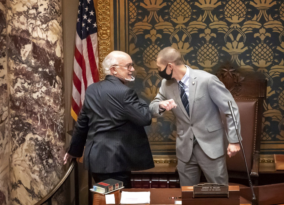 Photo -  In this Nov. 12 photo, outgoing Minnesota State Senate President Senate President Jeremy Miller gives Sen. David Tomassoni a congratulatory elbow bump before Tomassoni addresses the Senate Chamber in St. Paul, Minn. [Glen Stubbe/Star Tribune via the Associated Press]