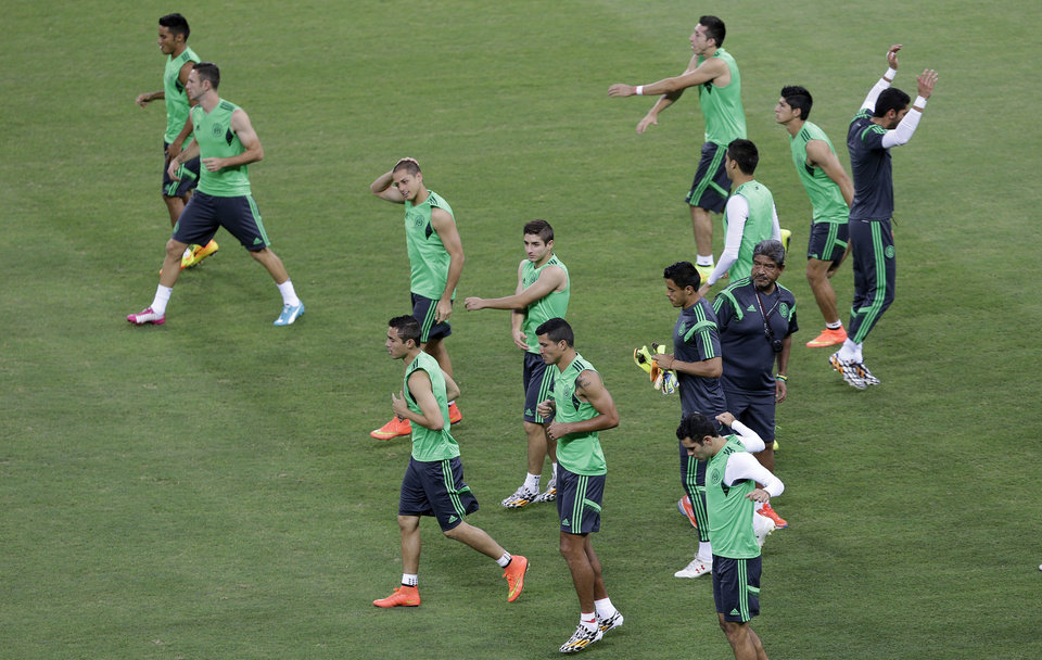Photo - Mexican players exercise during an official training session the day before the group A World Cup soccer match between Brazil and Mexico, at the Arena Castelao in Fortaleza, Brazil, Monday, June 16, 2014. (AP Photo/Andre Penner)