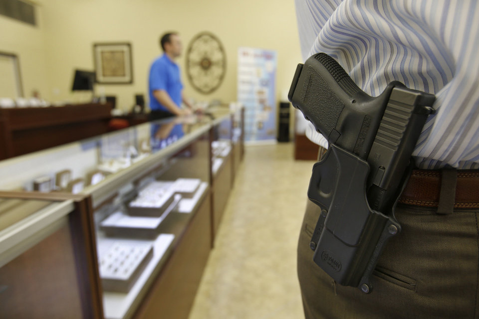 Guns are an important line of security at Absolute Diamond & Gold Buyers in Oklahoma City, said co-owner Will Miller, standing behind counter. He said the business will continue to allow customers to carry their weapons concealed on Nov. 1, but only a designated security officer will carry his gun openly. Photo by Steve Gooch, The Oklahoman