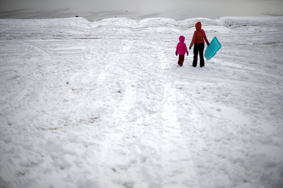 Photo - Two people get up after sledding down a hill after a winter storm left a blanket of snow on the ground outside a northwest Oklahoma City area neighborhood near 164th and Pennsylvania, Friday, December 6, 2013. Photo by Bryan Terry, The Oklahoman