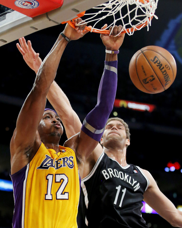Photo -   Los Angeles Lakers' Dwight Howard (12) dunks against Brooklyn Nets' Brook Lopez (11) in the first half of an NBA basketball game in Los Angeles, Tuesday, Nov. 20, 2012. (AP Photo/Jae C. Hong)