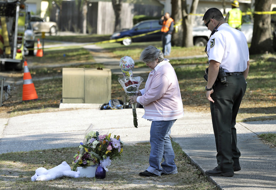 Photo - Brenda Bush is escorted by a Hillsborough County Sheriff's deputy as she places flowers, Saturday, March 2, 2013,  at a makeshift memorial in front of a home where a sinkhole opened up underneath a bedroom late Thursday evening and swallowed her son Jeffrey in Seffner, Fla.  Jeffrey Bush, 37, was in his bedroom Thursday night when the earth opened and took him and everything else in his room. Five other people were in the house but managed to escape unharmed. Bush's brother jumped into the hole to try to help, but he had to be rescued himself by a sheriff's deputy. (AP Photo/Chris O'Meara)