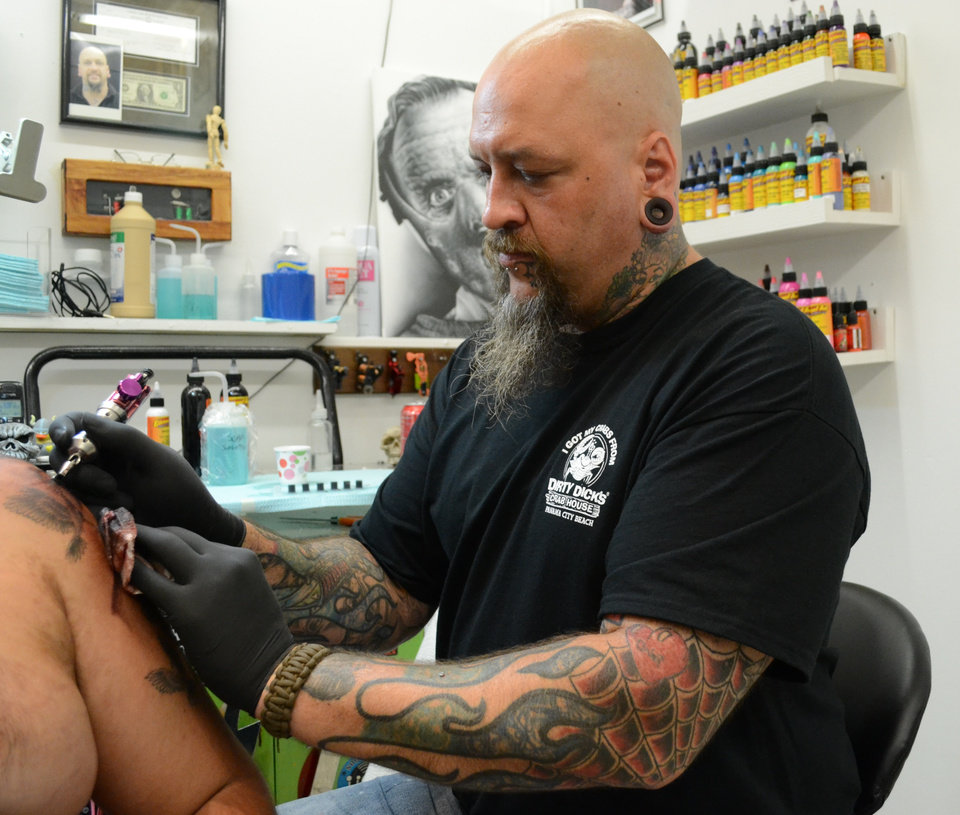 "In this Thursday, June 27, 2013, photo, former Fort Knox soldier ""Baldy"" Carder inks a customer's arm at his Radcliff, Ky., tattoo parlor. Businesses like Carder's could be affected by the recent move by the Army to eliminate a brigade of about 3,300 soldiers at the famed Army post. (AP Photo/Dylan Lovan)"