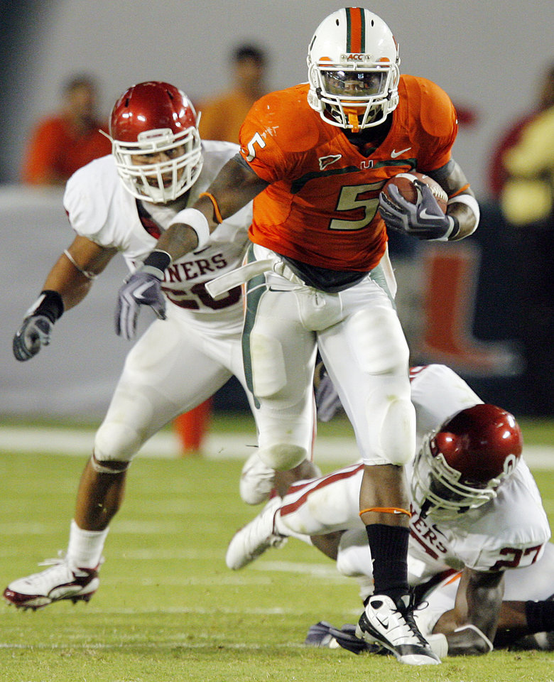 Photo - Miami's Javarris James (5) runs away from OU defenders Travis Lewis (28), left, and Sam Proctor (28), right, during the college football game between the University of Oklahoma (OU) Sooners and the University of Miami (UM) Hurricanes at Land Shark Stadium in Miami Gardens, Florida, Saturday, October 3, 2009. Miami won, 21-20. Photo by Nate Billings, The Oklahoman ORG XMIT: KOD