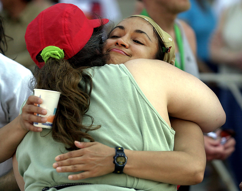 Photo - ALFRED MURRAH FEDERAL BUILDING CAR BOMB EXPLOSION: Andrea Sanchez gets a hug from Nina Gonzales, the niece of Tony Reyes who was killed in the bombing, after finishing Oklahoma City Memorial marathon Sunday afternoon.  Staff photo by Bryan Terry