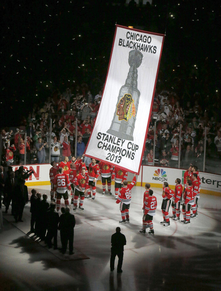 Photo - ADVANCE FOR USE SUNDAY, DEC. 22 AND THEREAFTER - FILE - In this Oct. 1, 2013 file photo, Chicago Blackhawks players watch as their Stanley Cup Championship banner is lifted to the rafters during ceremonies before an NHL hockey game between the Blackhawks and Washington Capitals in Chicago. The story was voted as one of the top 10 stories in Illinois for 2013. (AP Photo/Charles Rex Arbogast, File)