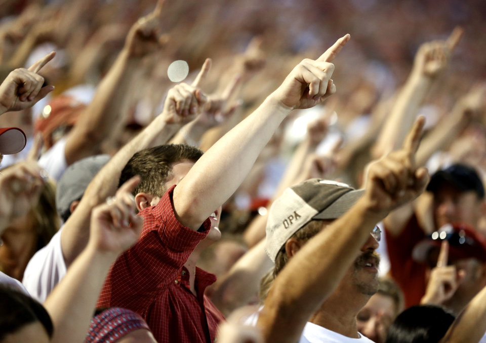Photo - Oklahoma fans sing the school's chant and raise their hands before a college football game between the University of Oklahoma Sooners (OU) and the Ohio State Buckeyes at Gaylord Family-Oklahoma Memorial Stadium in Norman, Okla., on Saturday, Sept. 17, 2016. Photo by Steve Sisney, The Oklahoman