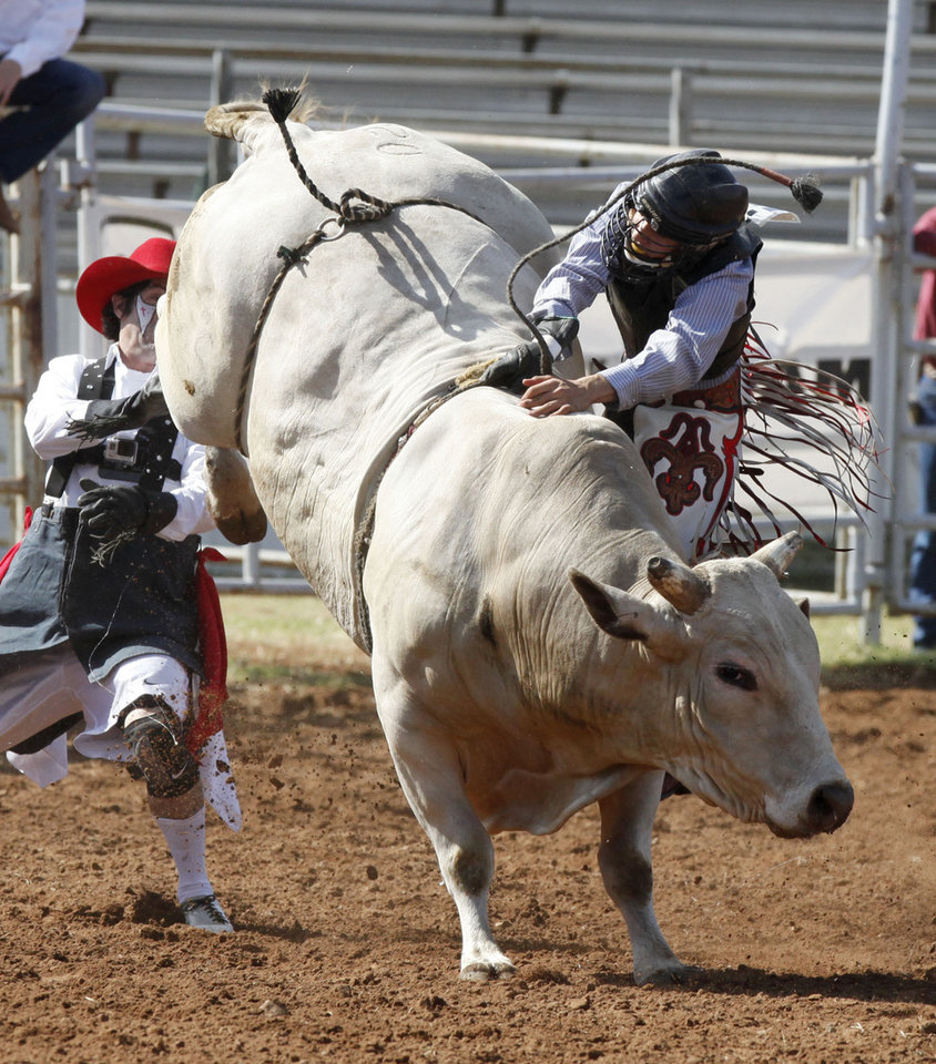 Photo - Koby Radley gets caught up in his rigging during the bull riding event of Tuesday's performances at the International Youth Finals Rodeo at the Shawnee Heart of Oklahoma Exposition Center in Shawnee, OK, Tuesday, July 8, 2014,  Photo by Paul Hellstern, The Oklahoman