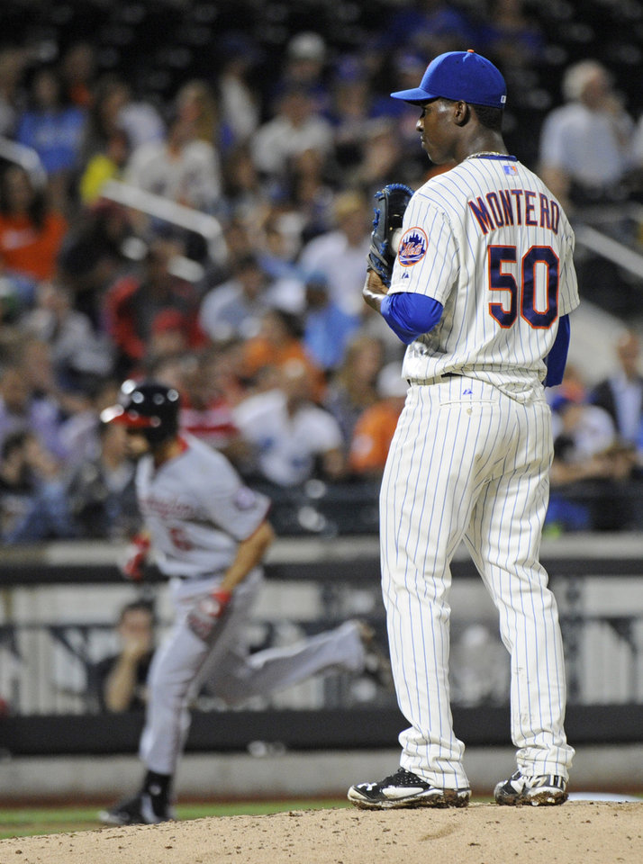 Photo - New York Mets pitcher Rafael Montero, right, looks on as Washington Nationals' Anthony Rendon rounds the bases after hitting a home run during the sixth inning of a baseball game against the New York Mets Tuesday, Aug.12, 2014, at Citi Field in New York. (AP Photo/Bill Kostroun)