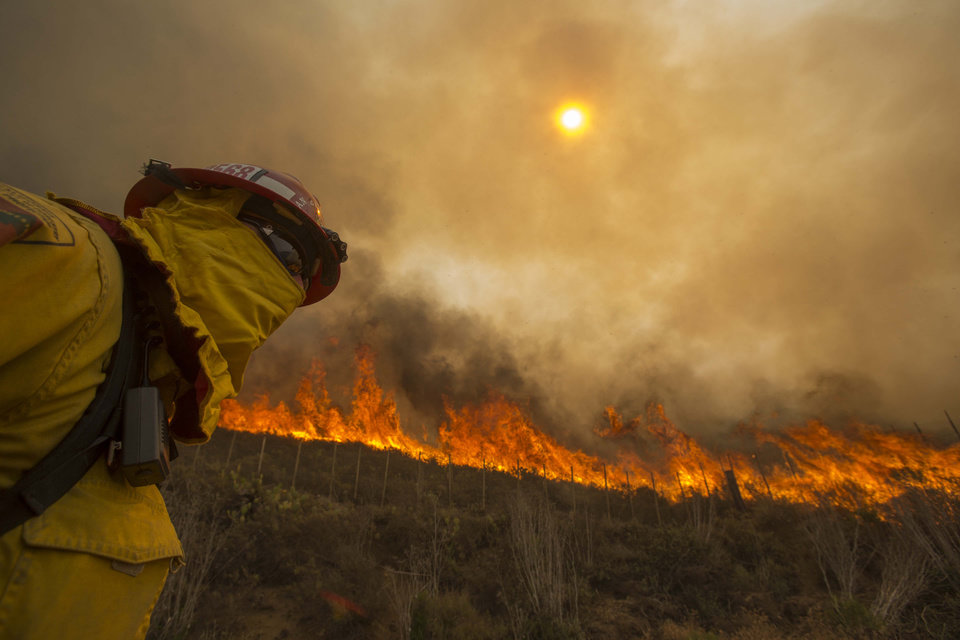 Photo - A firefighter keeps watch as the wildfire burns along a hillside in Point Mugu , Calif. Friday, May 3, 2013. Firefighters got a break as gusty winds turned into breezes, but temperatures remained high and humidity levels are expected to soar as cool air moved in from the ocean and the Santa Ana winds retreated. (AP Photo/Ringo H.W. Chiu)