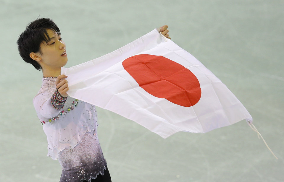 Photo - Yuzuru Hanyu of Japan poses with the national flag after he placed first in the men's free skate figure skating final following the flower ceremony at the Iceberg Skating Palace during the 2014 Winter Olympics, Friday, Feb. 14, 2014, in Sochi, Russia. (AP Photo/Vadim Ghirda)