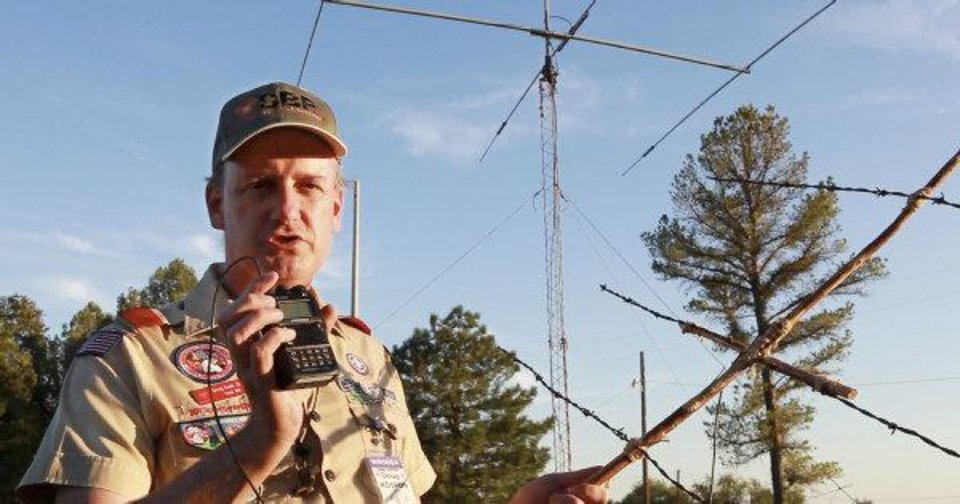 Photo - Doug Cook, with the Radio Scouter Group, holds a barb wire antena and a 5 wat radeo he used to contact the International Space Station last weekend during the 54th Jamboree-On-The -Air at John Nichols Scout Ranch.  David McDaniel - THE OKLAHOMAN