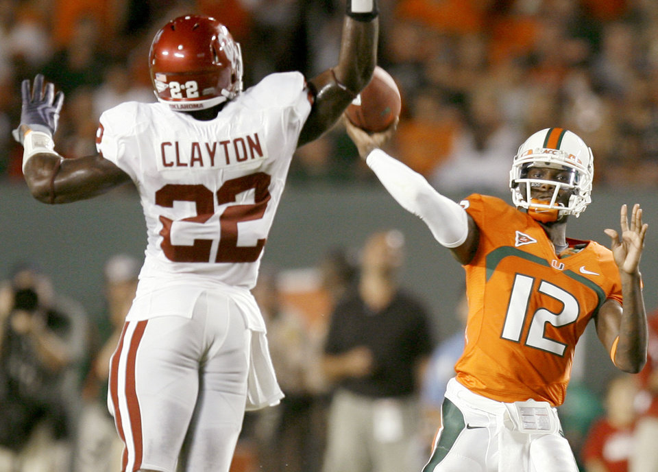 Photo - Miami's Jacory Harris throws a touchdown pass past OU's Keenan Clayton during the college football game between the University of Oklahoma (OU) Sooners and the University of Miami (UM) Hurricanes at Land Shark Stadium in Miami Gardens, Florida, Saturday, October 3, 2009. Photo by Bryan Terry, The Oklahoman