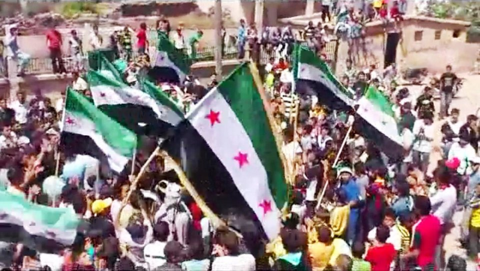 Photo -   In this image made from amateur video released by the Shaam News Network and accessed Wednesday, May 2, 2012, protesters carry Syrian revolutionary flags during a demonstration in Daraa, Syria. Syrian activists said government forces clashed with army defectors in the country's north on Wednesday, causing casualties and further enflaming an area near the Turkish border where rebel fighters have tried to seize territory. (AP Photo/Shaam News Network via AP video) TV OUT, THE ASSOCIATED PRESS CANNOT INDEPENDENTLY VERIFY THE CONTENT, DATE, LOCATION OR AUTHENTICITY OF THIS MATERIAL