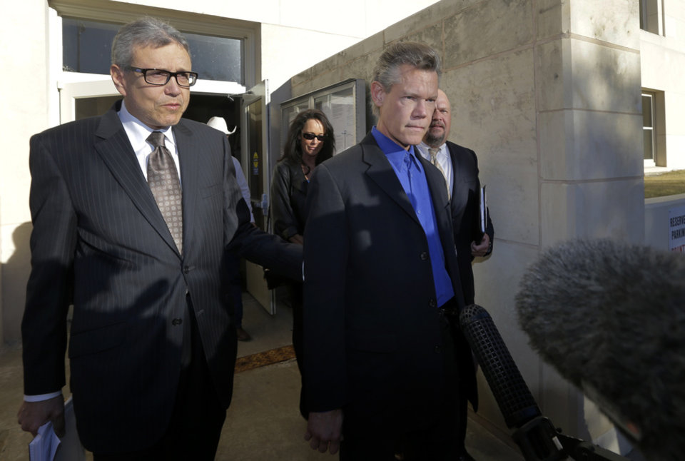 Photo - Entertainer Randy Travis, right, exits Grayson County Courthouse with attorney Larry Friedman, left, and other members of his legal team Thursday, Jan. 31, 2013, in Sherman, Texas. Travis plead guilty to driving while intoxicated in a plea agreement with the court and will pay a $2,000 fine and serve a two year probation. (AP Photo/Tony Gutierrez)