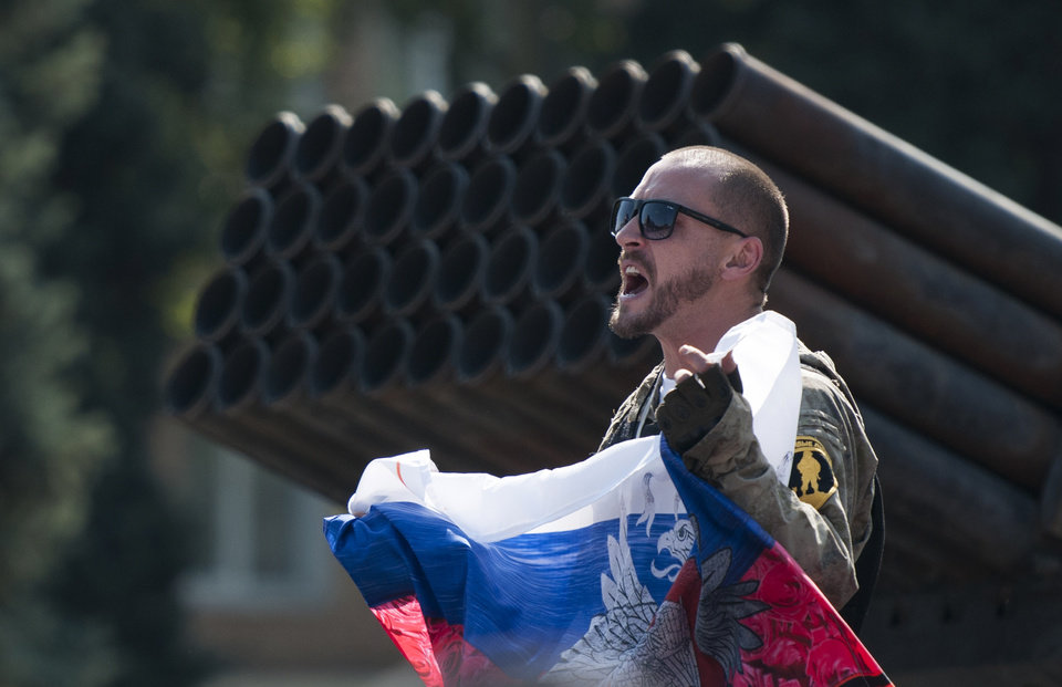 Photo - A pro-Russian rebel holds a Russian national flag near to damaged heavy hardware from the Ukrainian army during an exhibition in the central square in Donetsk, eastern Ukraine, Sunday, Aug. 24, 2014. Ukraine has retaken control of much of its eastern territory bordering Russia in the last few weeks, but fierce fighting for the rebel-held cities of Donetsk and Luhansk persists. (AP Photo/Antoine E.R. Delaunay)