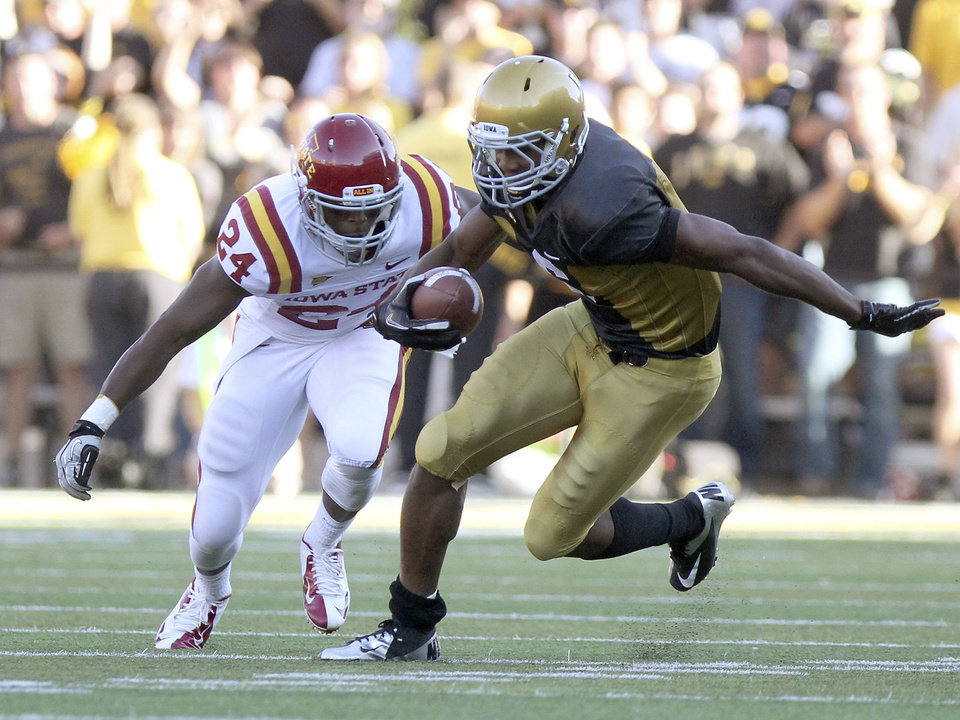 Photo -   Iowa receiver Keenan Davis scrambles past Iowa State's Durrell Givins for a first down during the fourth quarter of an NCAA college football game Saturday, Sept. 8, 2012, in Iowa City, Iowa. Iowa State won 9-6. (AP Photo/Conrad Schmidt)