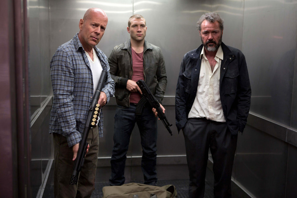 Photo - FILE - This publicity film image released by 20th Century Fox shows Bruce Willis as John McClane, left, Jai Courtney as his son Jack, center and Sebastian Koch as Komarov in a scene from