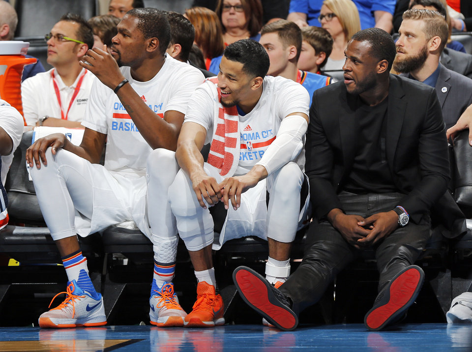 Photo - From left, Oklahoma City's Kevin Durant, Andre Roberson and Dion Waiters sit on the bench in the fourth quarter during Monday's game between the Thunder and Portland Trail Blazers at Chesapeake Energy Arena. Oklahoma City won, 128-94. (Photo by Nate Billings, The Oklahoman)
