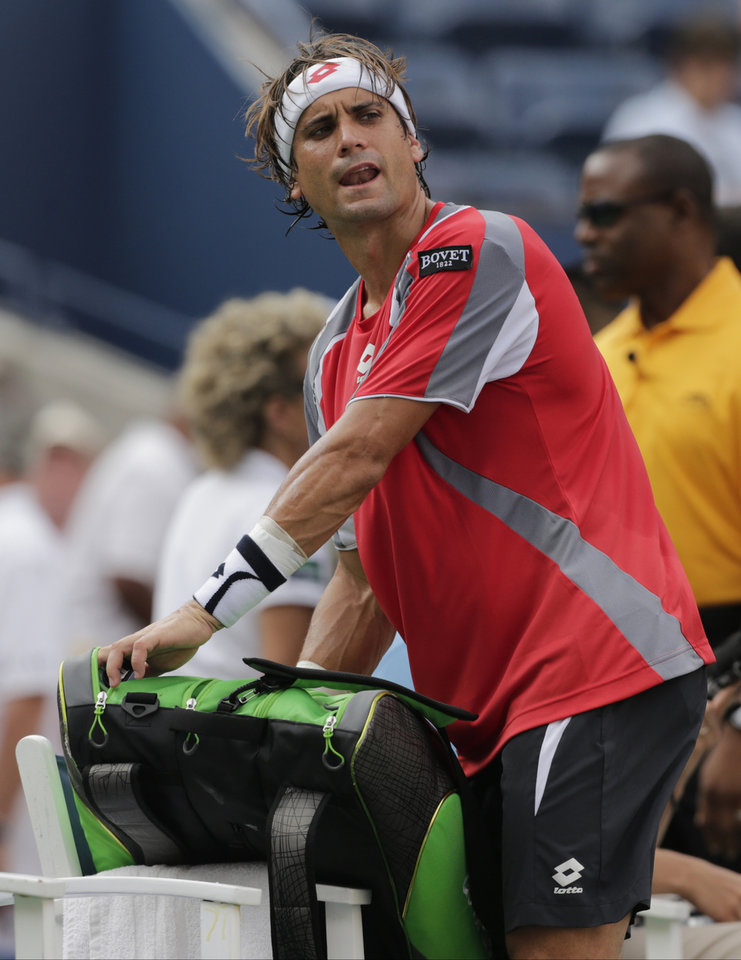 Photo -   Spain's David Ferrer comments as he packs up his gear after a semifinal match against Novak Djokovic, of Serbia, was postponed because of approaching inclement weather at the 2012 US Open tennis tournament, Saturday, Sept. 8, 2012, in New York. (AP Photo/Charles Krupa)