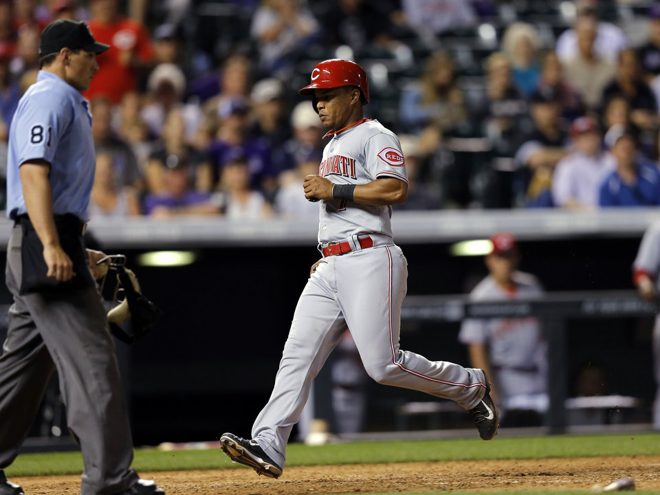 Photo - Cincinnati Reds' Ramon Santiago scores against the Colorado Rockies during the ninth inning of a baseball game Friday, Aug. 15, 2014, in Denver. (AP Photo/Jack Dempsey)