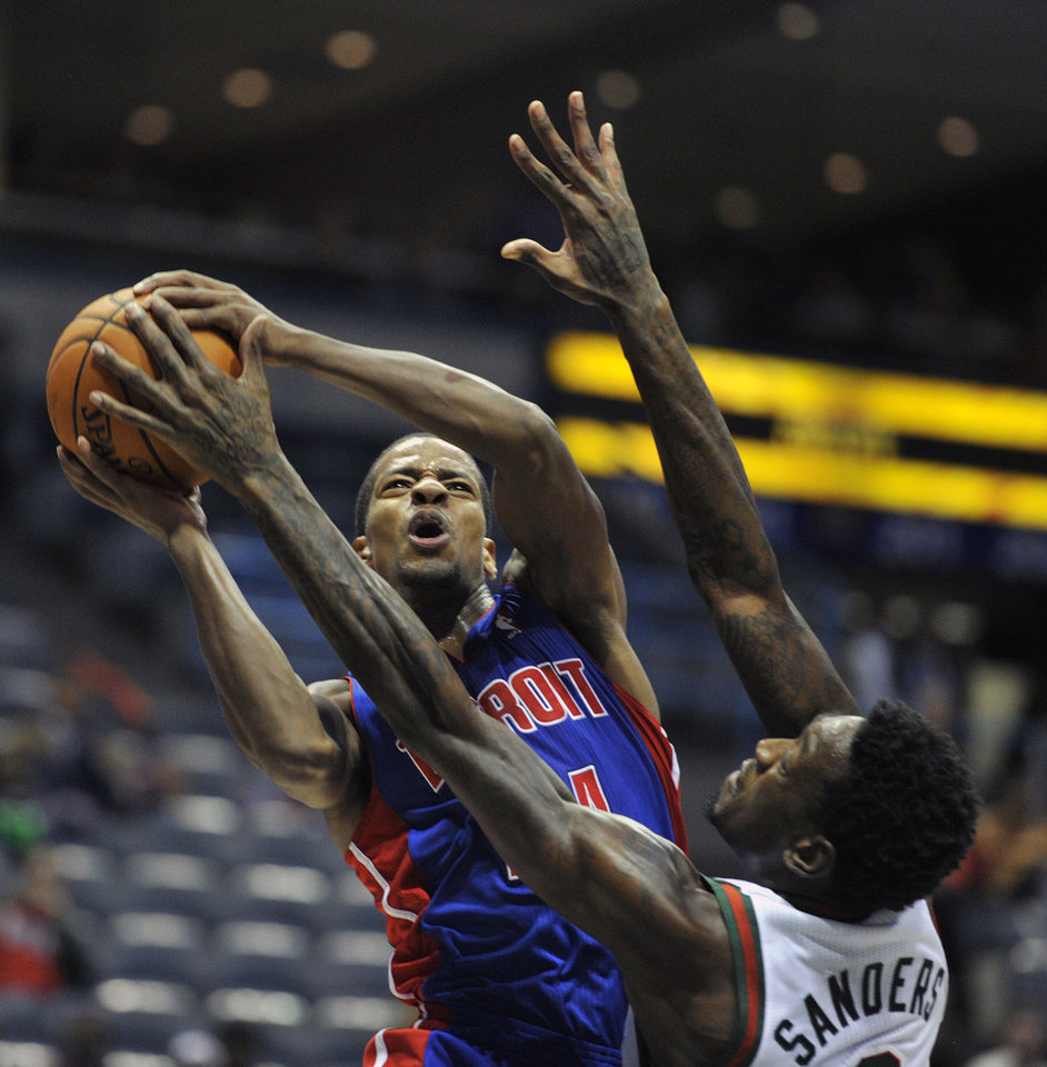 Detroit Pistons' Kim English, left, drives to the basket against Milwaukee Bucks' Larry Sanders during the first half of an NBA basketball game on Saturday, Oct. 13, 2012, in Milwaukee. (AP Photo/Jim Prisching)
