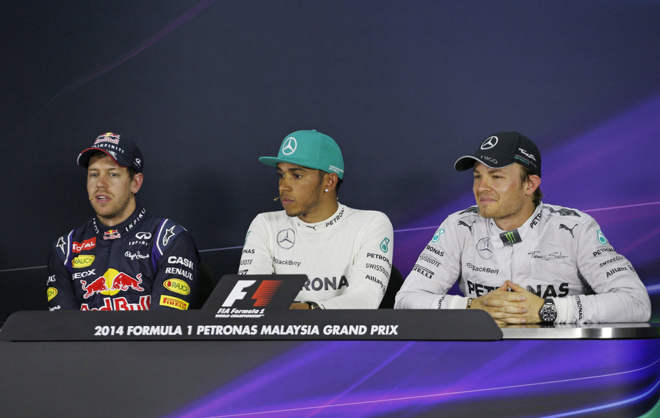 Photo - Red Bull Racing driver Sebastian Vettel, left, of Germany speaks as Mercedes drivers Lewis Hamilton, center, of Britain and Nico Rosberg, right, of Germany listen during a press conference after the qualifying session for Sunday's Malaysian Formula One Grand Prix at Sepang International Circuit in Sepang, Malaysia, Saturday, March 29, 2014. Hamilton took the pole position while Vettel with second position and Rosberg with third position. (AP Photo/Peter Lim)