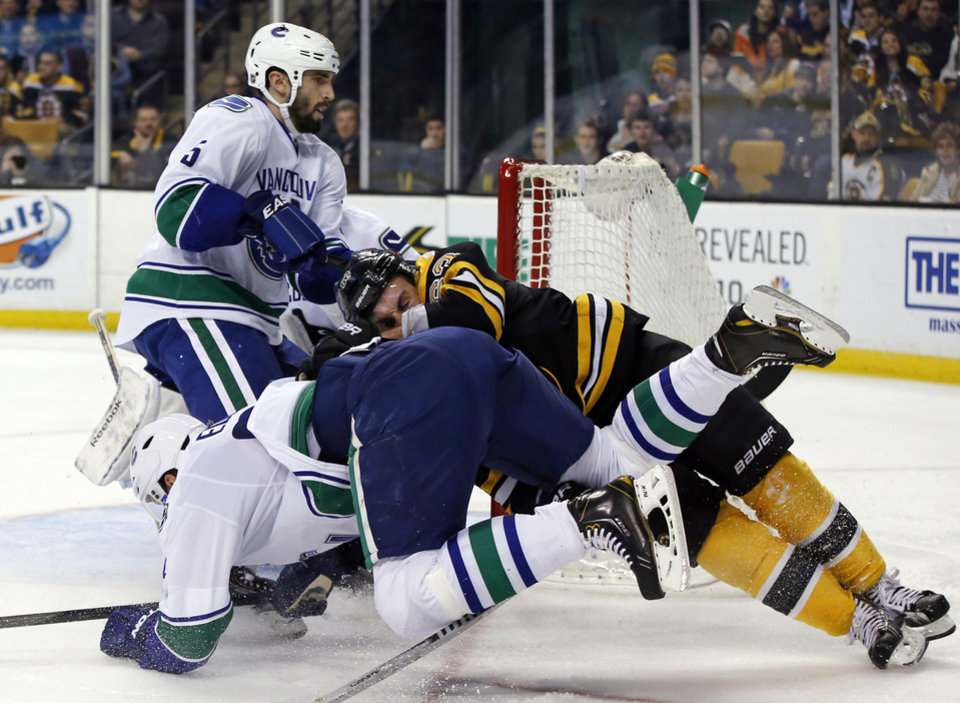 Photo - Boston Bruins left wing Brad Marchand, right, crashes with Vancouver Canucks defenseman Alexander Edler, front left, as he tries to score, while Canucks defenseman Jason Garrison (5) watches during the second period of an NHL hockey game in Boston on Tuesday, Feb. 4, 2014. (AP Photo/Elise Amendola)