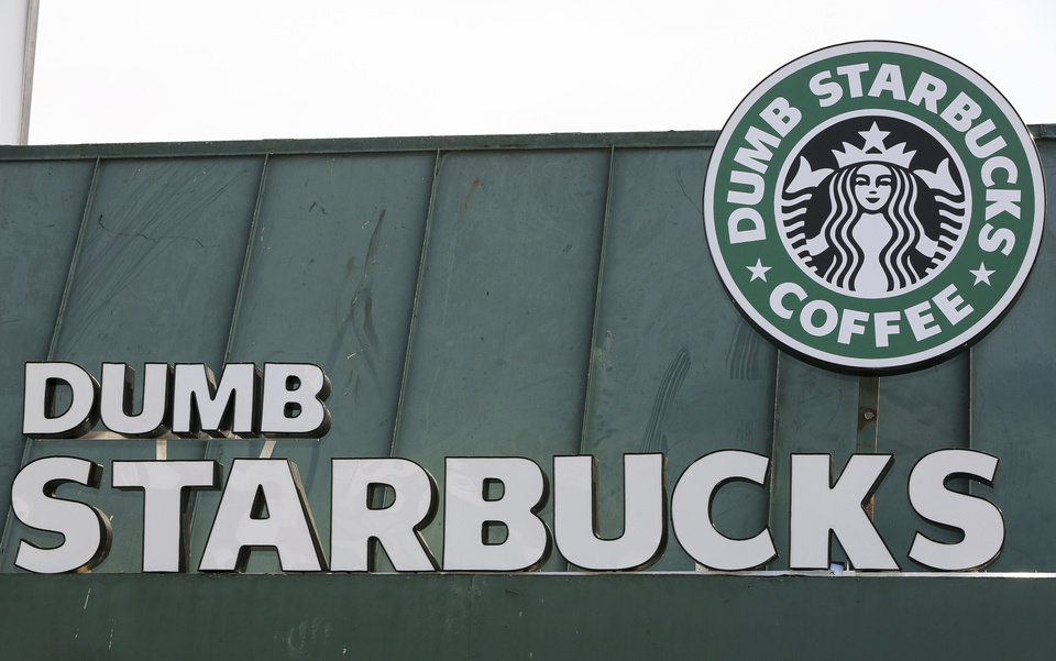 Photo - The sign at Dumb Starbucks coffee in Los Angeles, is displayed Monday, Feb. 10, 2014.  The store resembles a Starbucks with a green awning and mermaid logo, but with the word