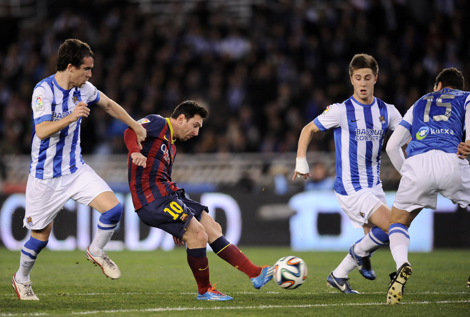 Photo - FC Barcelona's Lionel Messi of Argentina, center, shoots the ball to the goal between Real Sociedad's Jon Gaztanaga, right, and Mikel Gonzalez, left, during their Spanish Copa del Rey semifinal second leg soccer match, at Anoeta stadium, in San Sebastian northern Spain, Wednesday, Feb. 12, 2014. (AP Photo/Alvaro Barrientos)
