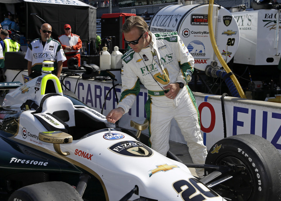 Photo - Pole-sitter Ed Carpenter looks over his car before the start of final day of practice for the Indianapolis 500 IndyCar auto race at the Indianapolis Motor Speedway in Indianapolis, Friday, May 23, 2014. The 98th running of the Indianapolis 500 is Sunday. (AP Photo/Michael Conroy)