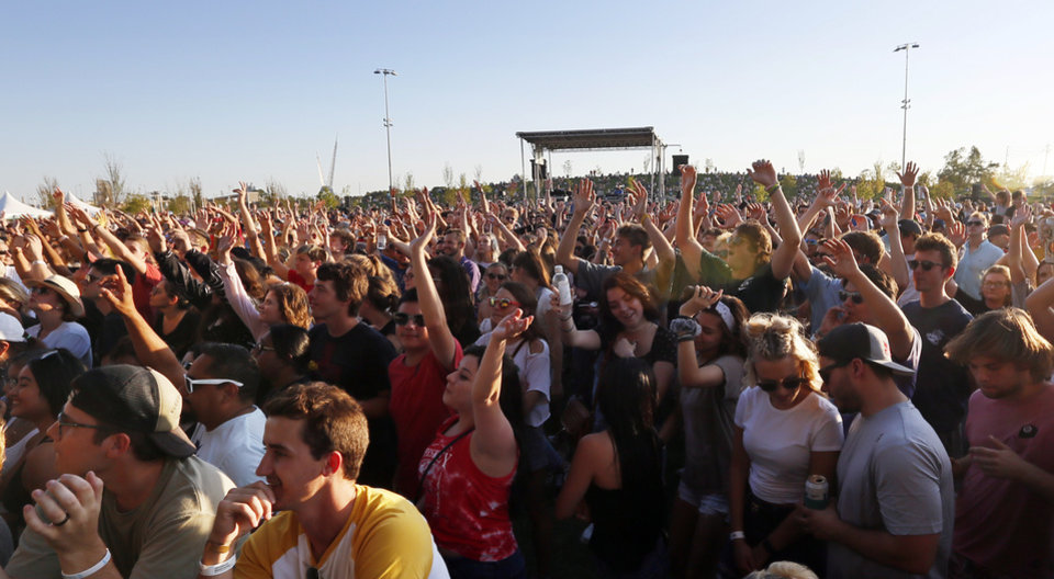 Photo - People in the crowd raise their arms as Republican Hair performs during the grand opening of Scissortail Park in Oklahoma City, Friday, Sept. 27, 2019. [Nate Billings/The Oklahoman]