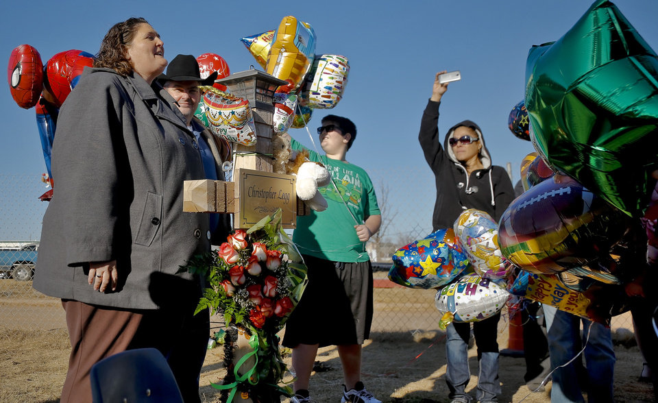 Photo - Danni Legg leads the singing of Happy Birthday while next to her son's, Christopher, wooden cross that stands outside the Plaza Towers Elementary School during a balloon release to mark what would have been Christopher's tenth birthday in Moore, Okla. on Thursday, Jan. 16, 2014. Christopher was killed along with six others when the May 20th tornado hit the school. Parents of those killed have been notified that the crosses will need to be removed for further rebuilding of the school. Photo by Chris Landsberger, The Oklahoman
