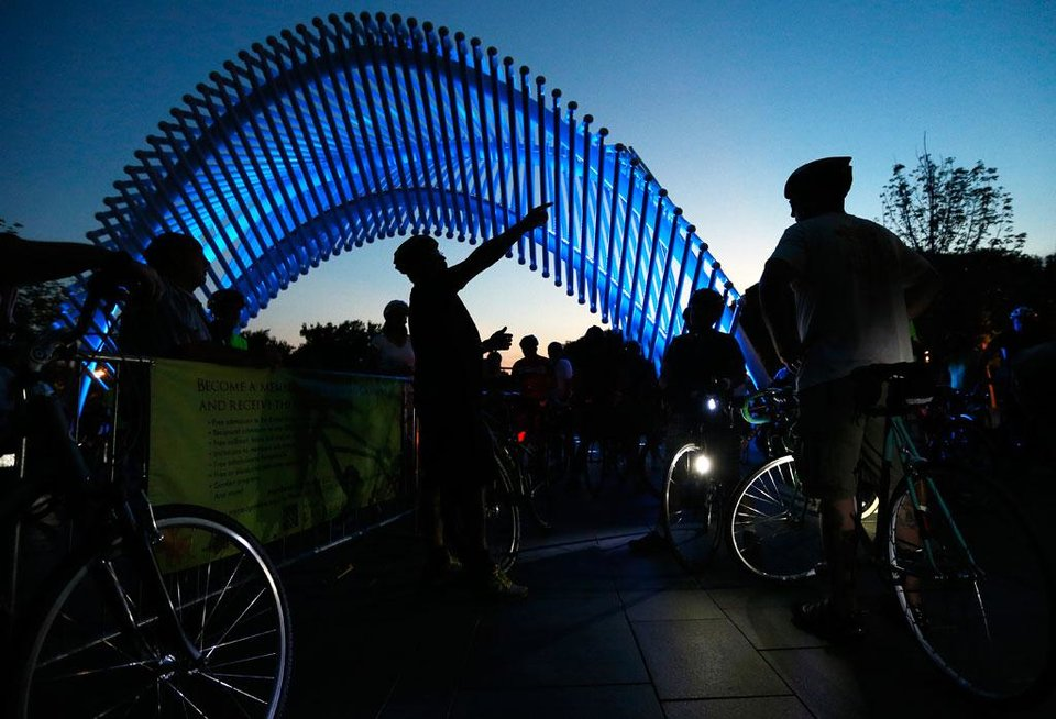 Photo -  A ride leader gives instructions to cyclists gathered at the Myriad Gardens for the Full Moon Bicycle Ride organized by the Myriad Gardens and Schlegel Bicycles in Oklahoma City, Monday, July 22, 2013. The next moonlight ride will be Tuesday, August 20, at 9pm starting at the Myriad Gardens' bandshell. Photo by Nate Billings, The Oklahoman
