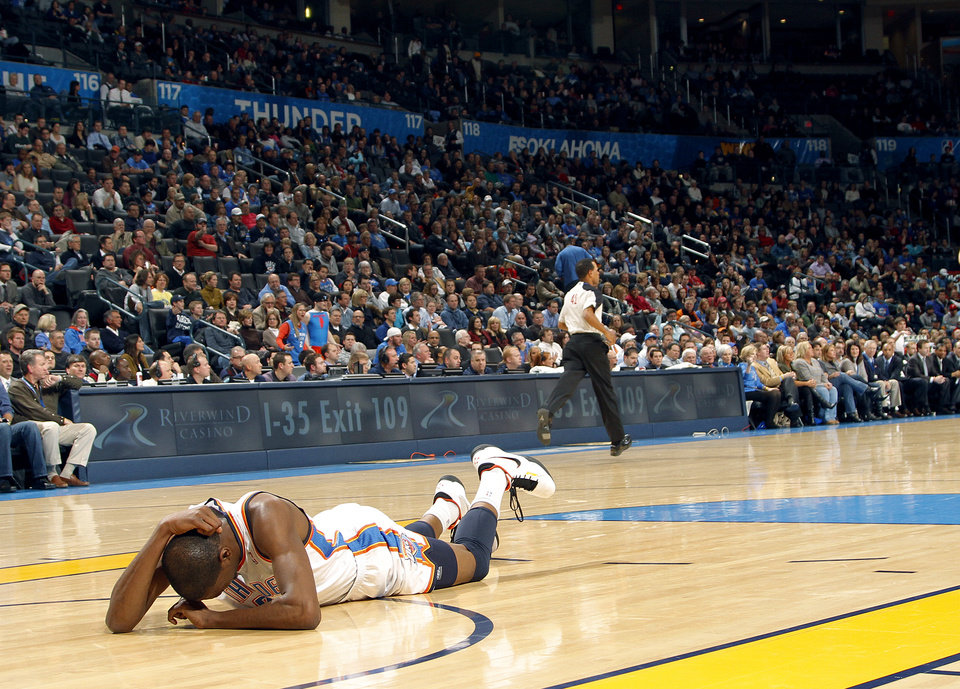 Photo - The Thunder's Kevin Durant lies on the court in pain after hitting his head during the NBA basketball game between the Oklahoma City Thunder and the Memphis Grizzlies at the Oklahoma City Arena on Tuesday, Feb. 8, 2011, Oklahoma City, Okla.Photo by Chris Landsberger, The Oklahoman