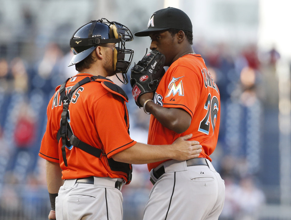 Photo - Miami Marlins catcher Jeff Mathis, left, talks with relief pitcher Arquimedes Caminero during the eighth inning of a baseball game against the Washington Nationals at Nationals Park, Thursday, April 10, 2014, in Washington. The Nationals won 7-1. (AP Photo/Alex Brandon)